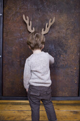 Young boy standing facing wall, cardboard reindeer cut out on wall behind him - CUF04061