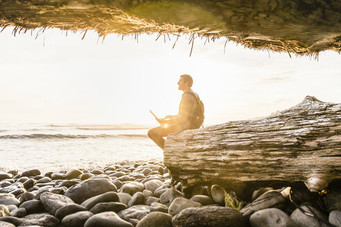Man sitting with laptop looking out from beach in Juan de Fuca Provincial Park, Vancouver Island, British Columbia, Canada - CUF04085