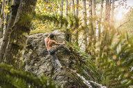 Male boulderer moving up forest boulder, Horne Lake Caves Provincial Park, Vancouver Island, British Columbia, Canada - CUF04091