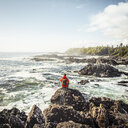 Male hiker looking out to sea from rocky coast, Wild Pacific Trail, Vancouver Island, British Columbia, Canada - CUF04094