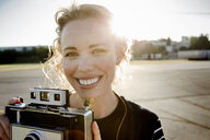 Portrait of mid adult woman in sunlight with vintage camera - CUF04226