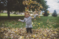 Portrait of red haired female toddler in park throwing autumn leaves - ISF00928