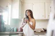 Young woman wrapped in towel looking through kitchen window - CUF04270