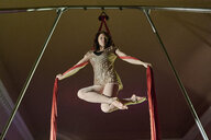 Low angle view of young female aerial acrobat poised with silk rope - CUF04387