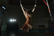 Young female acrobat poised hanging from hoop - CUF04390