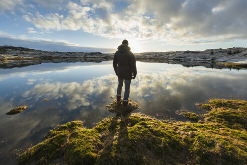 Man standing at water's edge, looking at view, rear view, Tjarnarholl, Iceland - CUF04414