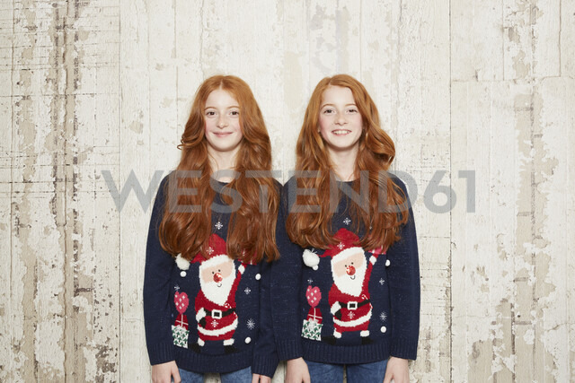 Portrait of twin sisters wearing Christmas jumpers - CUF04423