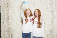 Portrait of twin sisters wearing Christmas jumpers, taking selfie using smartphone - CUF04426