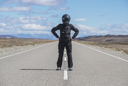 Woman in motorbike clothes standing in the middle of Route 40 - the longest road in South America, El Chalten, Route 40, Santa Cruz province, Argentina - CUF04462