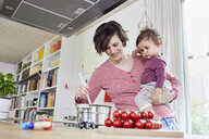 Mother holding baby girl in kitchen, whilst stirring pot on stove - ISF01029