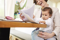 Mother looking at paperwork with baby girl sitting on her lap - ISF01035