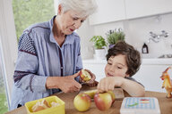 Grandmother and grandson preparing food in kitchen - ISF01044