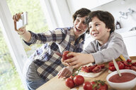 Mother and son preparing food in kitchen, mother taking selfie using smartphone - ISF01053
