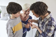 Mother putting plaster on son's finger, grandmother holding grandson's hand - ISF01056