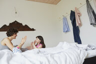 Mother and daughter playing in bedroom, smiling - ISF01059