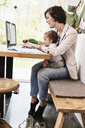 Mother holding sitting with baby daughter, working on laptop - ISF01092