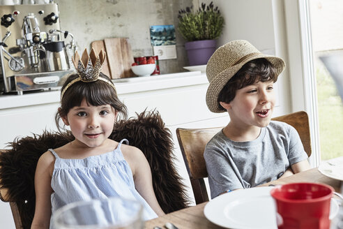 Brother and sister sitting at dinner table, smiling - ISF01110