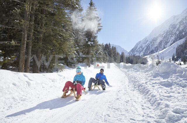Couple sledding in snow-covered landscape - CVF00473