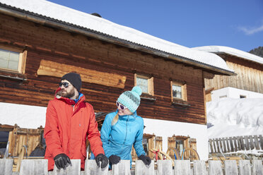 Couple in winter at wooden mountain hut looking around - CVF00482