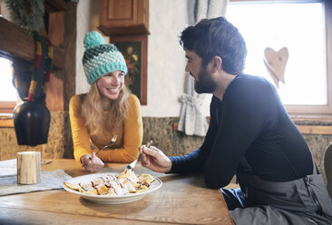 Happy couple eating in rustic mountain hut - CVF00491