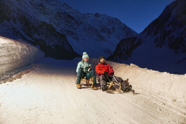 Couple sledding in snow-covered landscape at night - CVF00494