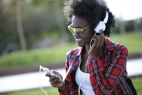 Portrait of happy young woman listening music with headphones and smartphone - JSRF00045