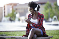 Smiling young woman sitting on bench in city park listening music with headphones - JSRF00048