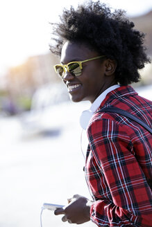 Portrait of smiling young woman with headphones and smartphone wearing mirrored sunglasses - JSRF00051