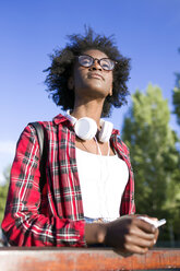 Portrait of young woman with headphones and cell phone - JSRF00069
