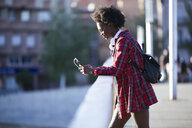 Young woman with headphones and backpack standing on a bridge using cell phone - JSRF00072