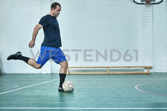 Man playing indoor soccer shooting the ball - ZEDF01411