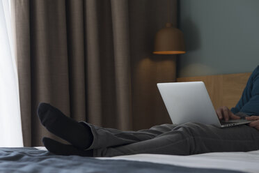 Young man lying on bed using laptop, partial view - SKCF00452