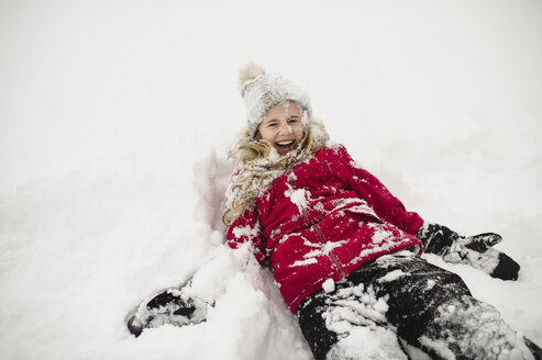 Smiling girl lying on back and covered in snow - CUF04535