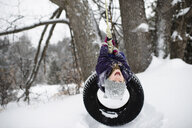 Girl upside down on tire swing in snow - CUF04538