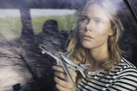Young woman with toy airplane gazing through car window - CUF04577
