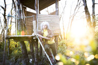 Mature woman leaning against woodland treehouse ladder at sunset - CUF04583