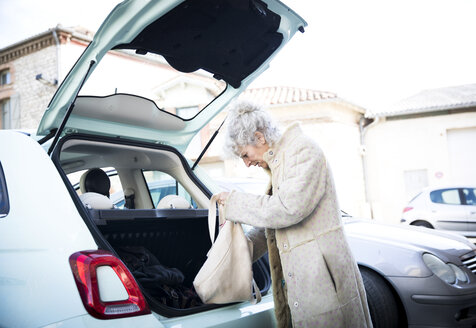 Mature woman with shopping bag looking in car trunk - CUF04592