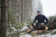 Logger taking break on logs, Tammela, Forssa, Finland - CUF04661