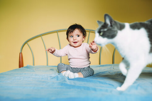 Surprised baby girl with cat on the bed - GEMF01967