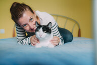 Happy woman with a black and white cat on the bed - GEMF01970