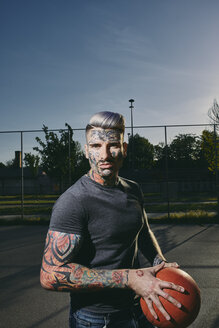 Portrait of tattooed young man with basketball on court - ZEDF01429