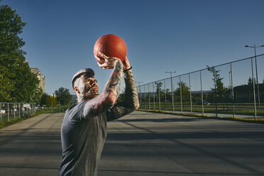 Tattooed young man throwing basketball on outdoor court - ZEDF01432