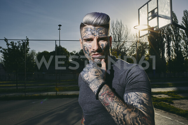 Portrait of tattooed young man on basketball court - ZEDF01435