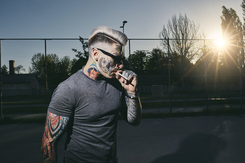 Tattooed young man wearing sunglasses smoking a cigarette - ZEDF01441