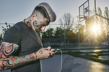 Tattooed young man with smartphone and earbuds - ZEDF01447