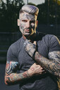 Portrait of tattooed young man outdoors - ZEDF01450