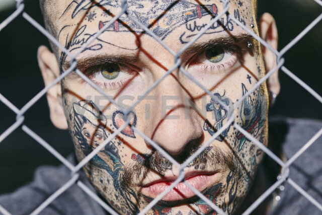 Tattooed face of young man behind fence - ZEDF01456