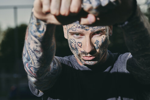 Portrait of tattooed young man outdoors clenching his fists - ZEDF01462