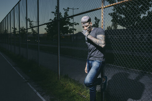 Tattooed young man smoking a cigarette at wire mesh fence - ZEDF01465