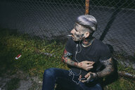 Tattooed young man with earbuds and smartphone smoking a cigarette at wire mesh fence - ZEDF01468